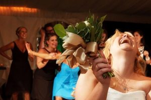 All the single ladies clamour to catch the bride's bouquet