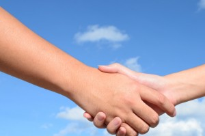Hand shake between a man and a woman on blue sky background