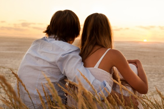 Couple Looking at Sunset On Beach