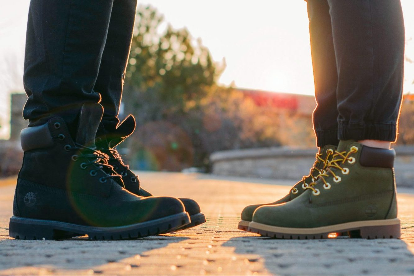 two people wearing boots facing one another