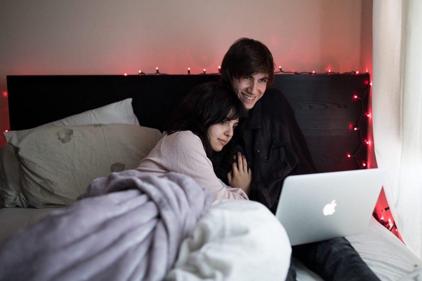 couple on bed using macbook