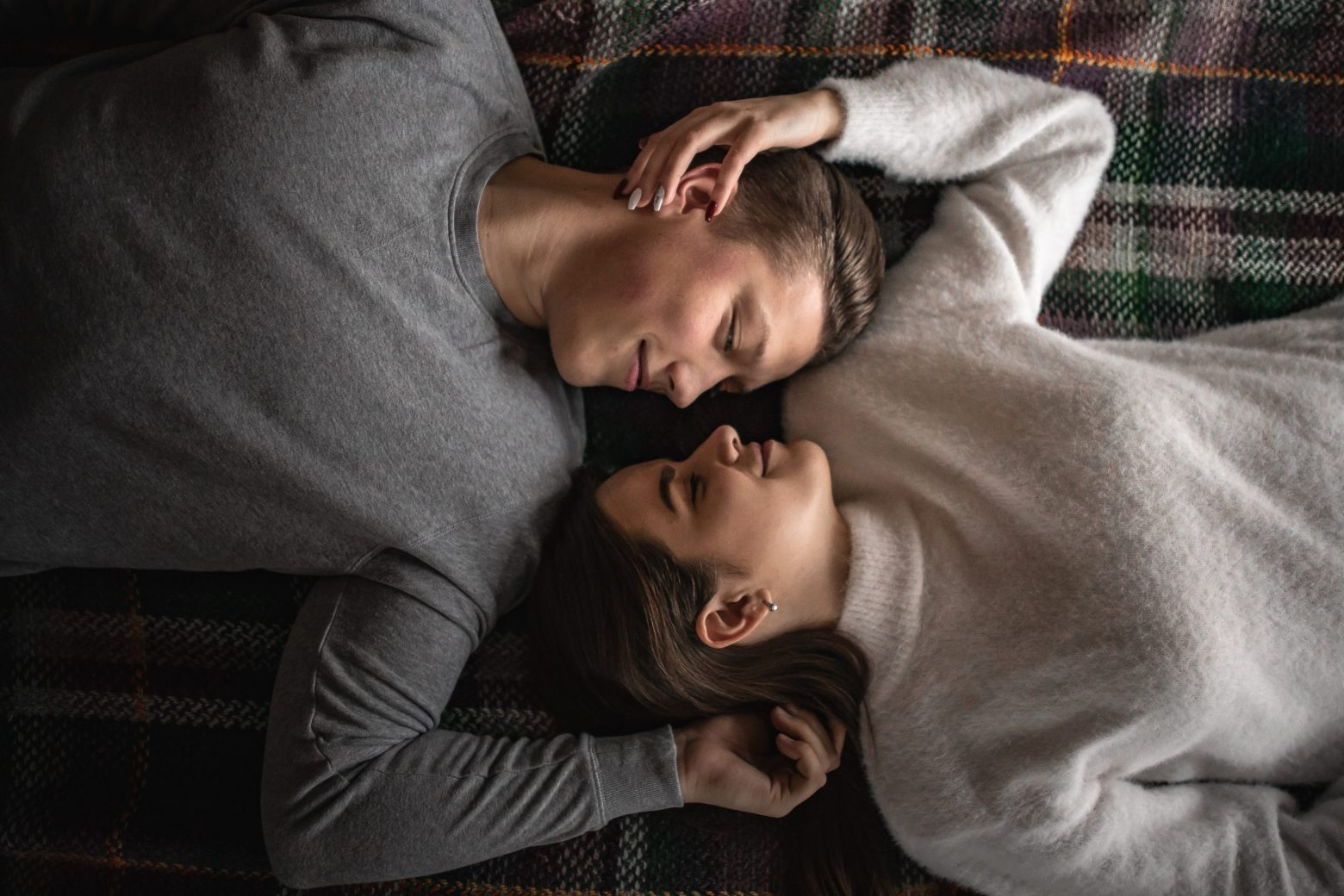 man and woman lying on bed together